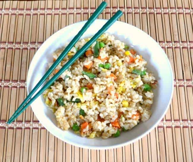 veggie fried rice in a white bowl with blue chopsticks on the edge of the bowl on a bamboo mat