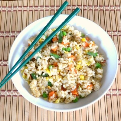 Veggie Fried Rice in white bowl with blue chopsticks