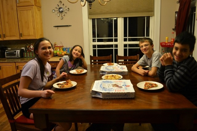 4 kids eating pizza at dining room table