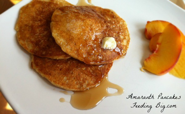 Amaranth Pancakes next to peach slices on a white plate