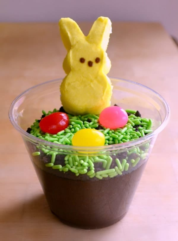 chocolate pudding in a clear cup topped with green sprinkles, jelly beans and a yellow peep