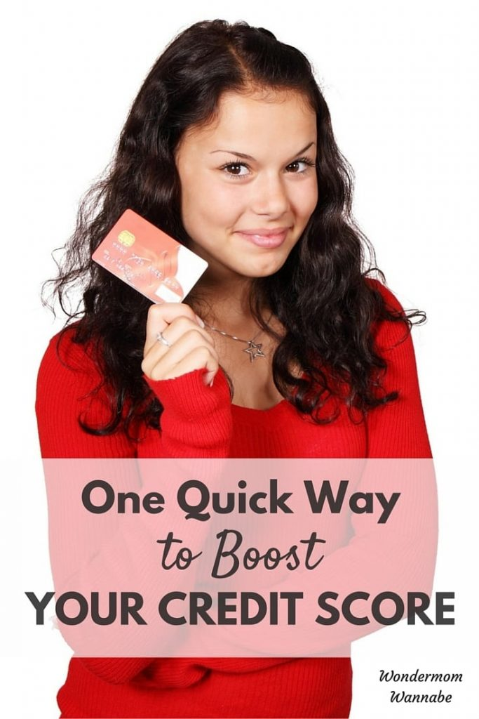 a lady holding a credit card with title text reading One Quick Way to Boost Your Credit Score