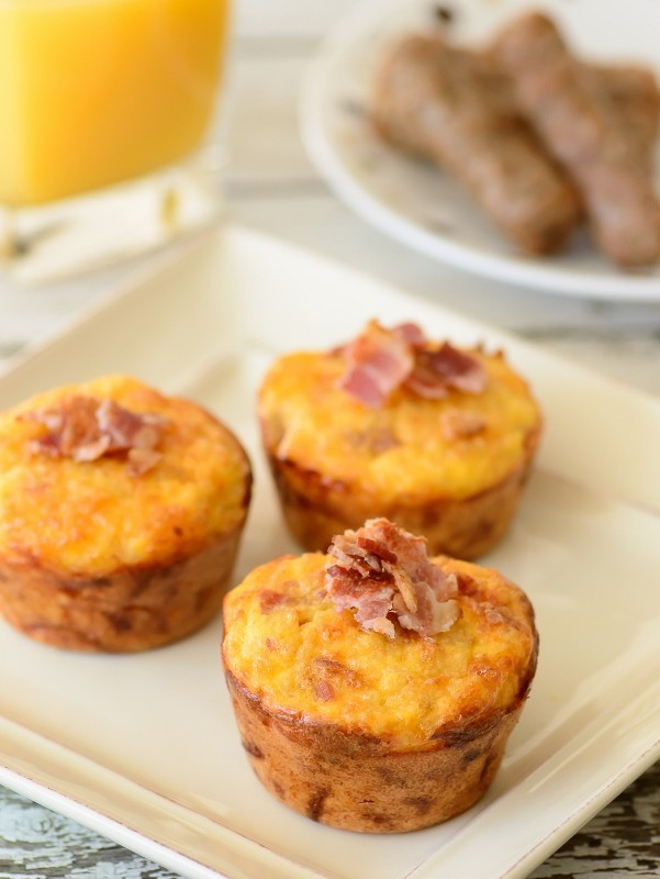 quinoa breakfast muffins on a plate with a glass of orange juice and a plate of sausage links in the background