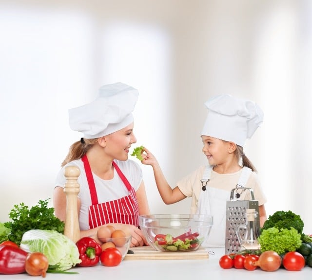 a mom and daughter cooking with vegetables