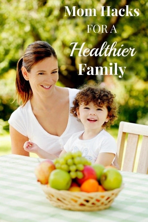 Mom and daughter smiling together outside with a bowl of fruit in front of them