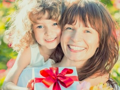 Mom and daughter smiling and holding a wrapped gift and flowers