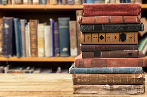 Books, old, stacked on a wood table with more old books on a bookshelf in the background
