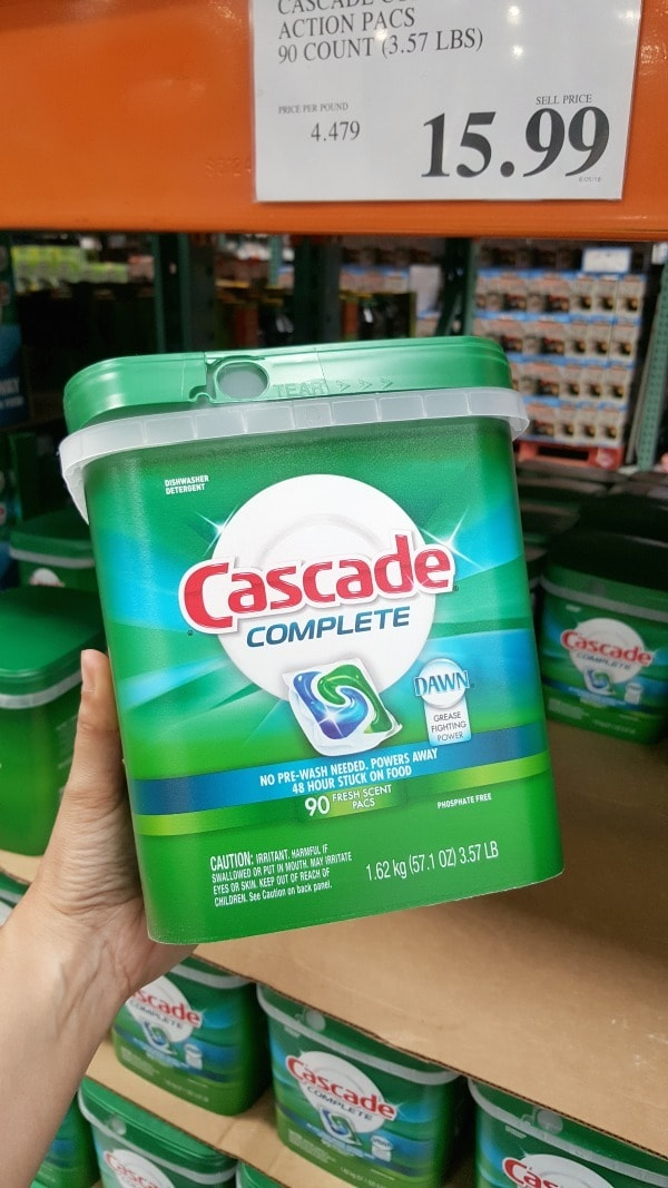 a person holding a container of Cascade Complete Pacs at Costco
