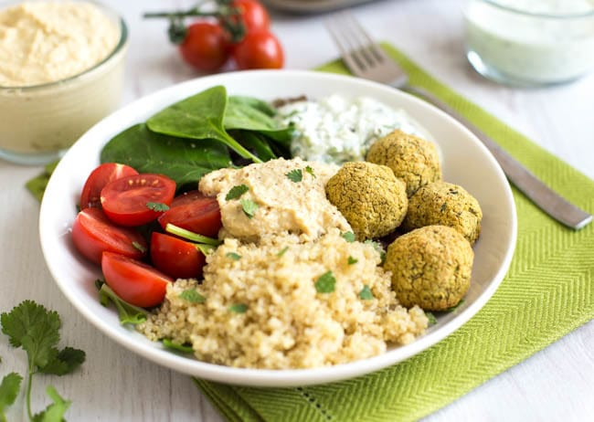 Homemade-falafel-quinoa-bowls in a white bowl next to a fork with some tomatoes and other ingredients in the background