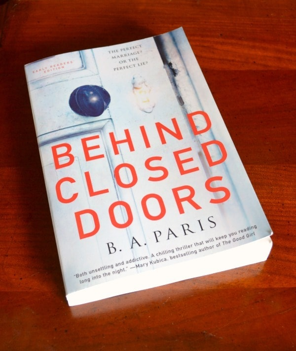 Behind Closed Doors book on a brown table