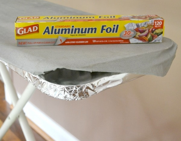 an ironing board wrapped in aluminum foil with a box of aluminum foil on top of it