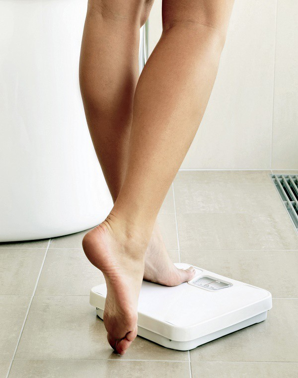 a lady stepping on a scale in a bathroom