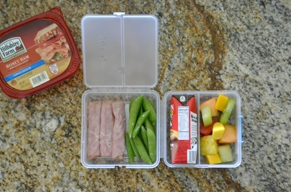 Ham and cream cheese roll ups, snap peas, milk carton, fruit in a plastic lunch box next to a tub of hillshire farm lunchmeat on a brown counter