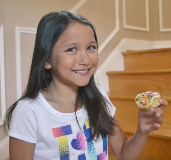 a girl smiling holding a  make ahead breakfast casserole cup with stairs in the background