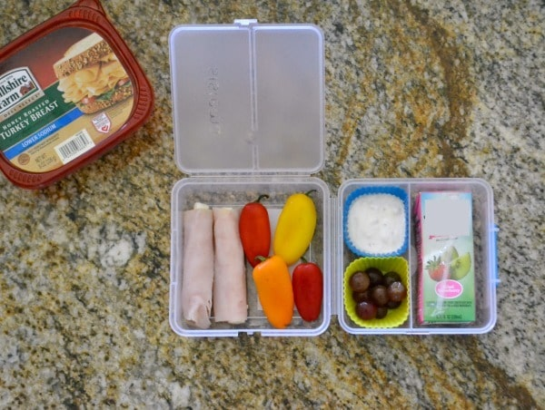 Turkey and cheese roll ups, bell peppers, fruit, ranch, juice box in a plastic lunch box next to a tub of hillshire farms turkey lunchmeat on a brown counter