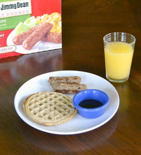 Turkey sausage with a whole wheat waffle and orange juice on a brown table