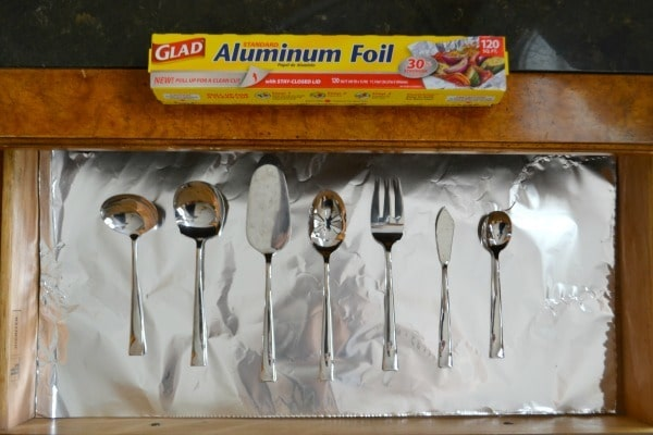 You can protect your silver from tarnishing by lining the storage drawer with aluminum foil.