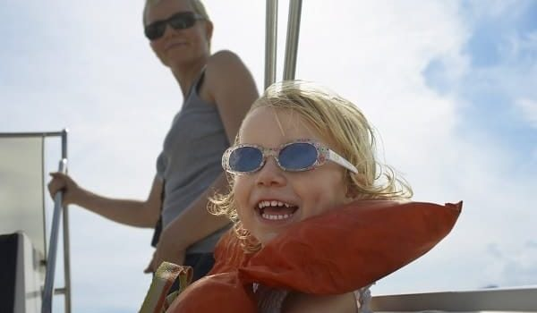 Girl (5-6) with mother on yacht, focus on foreground