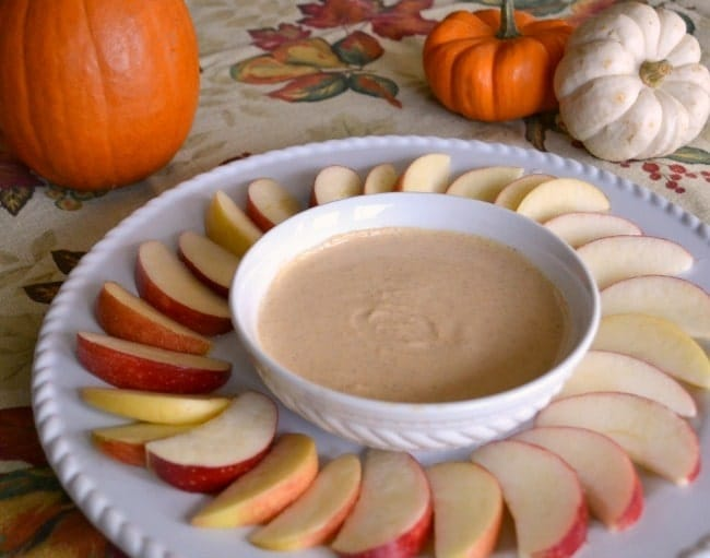 sliced apples next to a white bowl of pumpkin pie dip on a white tray next to pumpkins on a Fall tablecloth