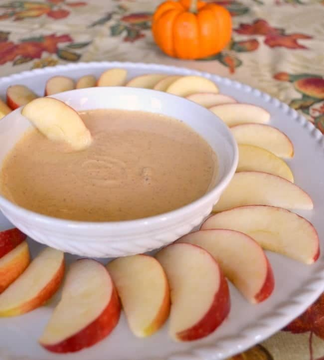 sliced apples on a plate with a bowl of pumpkin pie dip in the center on a leaf tablecloth with a small pumpkin in the background