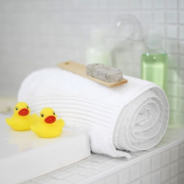 rubber ducks, a rolled up towel, shampoo and conditioner in a bathroom