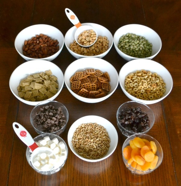items for a trail mix buffet in bowls on a brown table