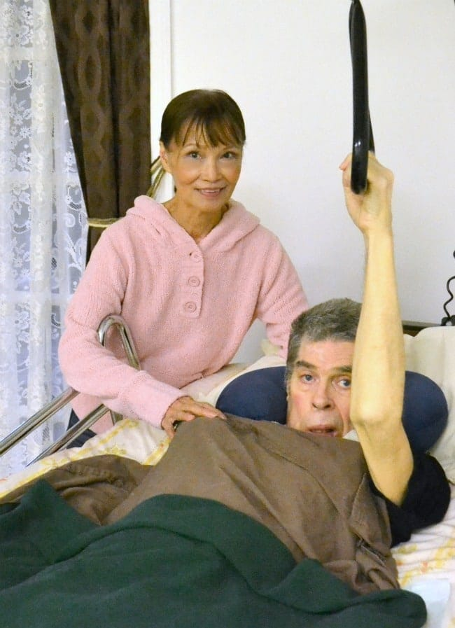dad in a hospital bed with the mom standing next to him