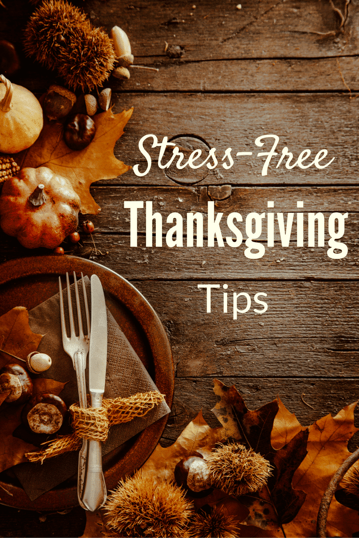 leaves, pumpkins, and gourds on a brown table, a plate with silverware on it, with title text reading stress-free Thanksgiving tips.