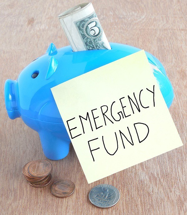 a blue piggy bank with a five dollar bill sticking out of it with a sticky note on it reading emergency fund next to coins on a brown table