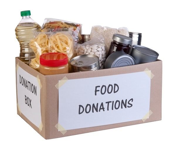 canned food and dry goods in a cardboard box labelled Donation Box and Food Donations