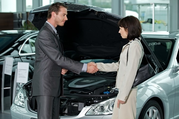 a man and a lady shaking hands in front of a car after learning How to get the best deal on a new car