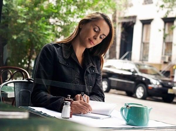 Woman Writing at Sidewalk Cafe