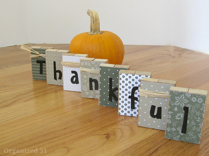 thankful-blocks next to a pumpkin on a brown table