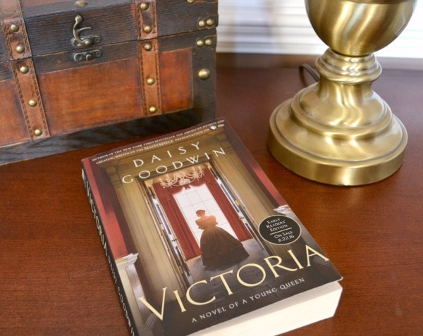 a book titled Victoria on a brown table next to a wooden chest and a brass lamp
