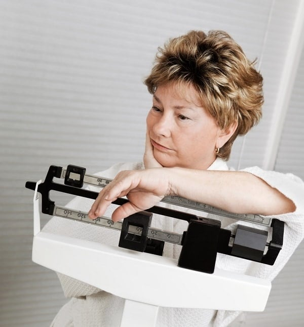 Mature woman looks disappointed at her progress losing weight, on weight scale.