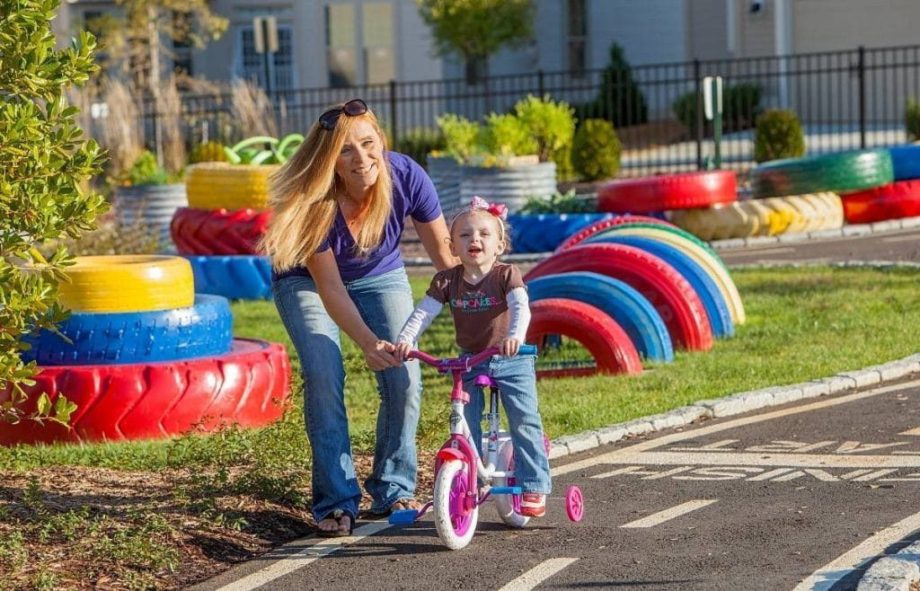 a girl riding a bike with the help of her mom in a racetrack-park