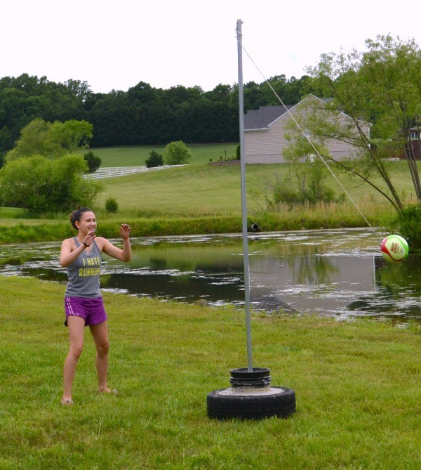 a teen girl playing tetherball outside next to a pond