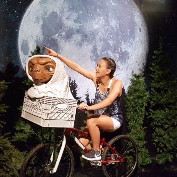 a teen girl sitting on a bike with E.T. at a wax-museum
