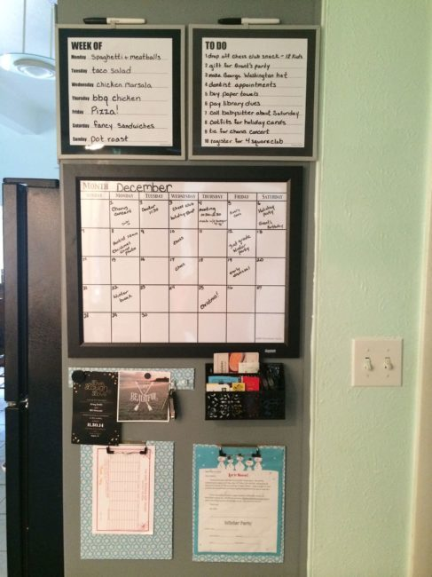 a command center on a wall in a home with a clipboard, calendar, menu white board and to do list whiteboard