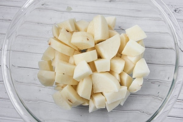 diced peeled potatoes in a glass bowl on a white wood table
