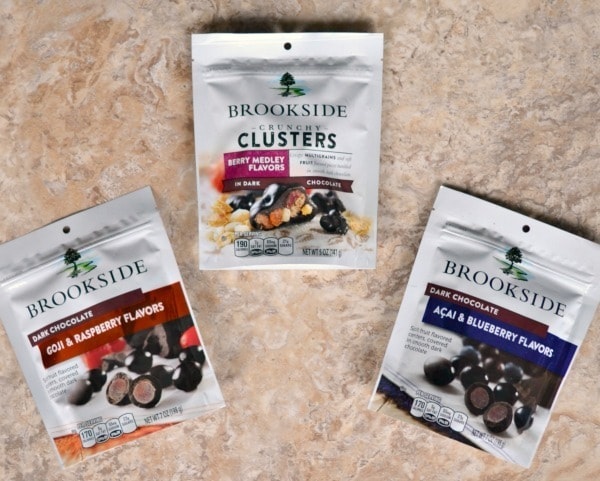 three different bags of Brookside Chocolates on a brown background