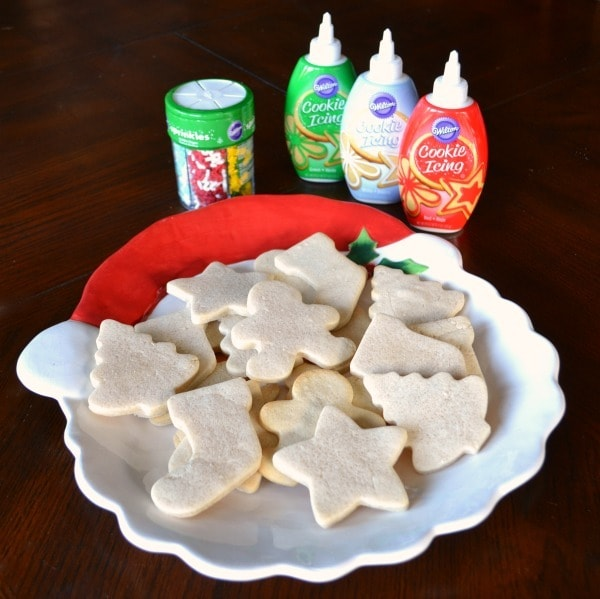 sugar cookies in Christmas shapes on a Santa plate next to three bottles of cookie icing and a jar of sprinkles on a brown table