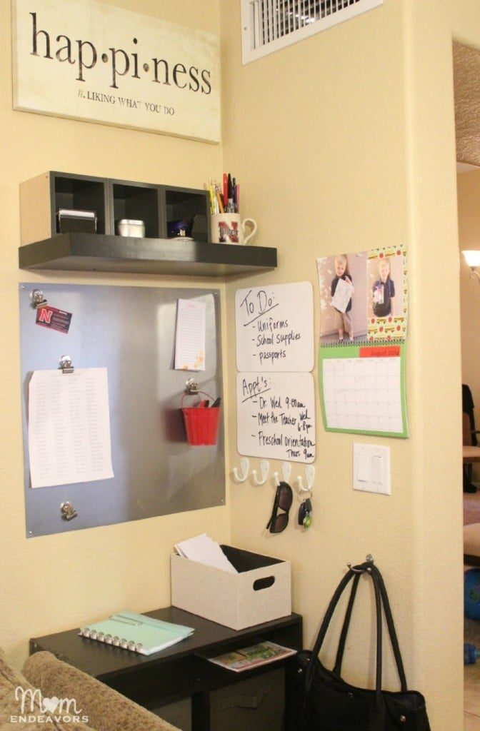a command center wall in a home with a shelf, calendar, metal board and white boards