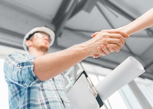 a construction worker shaking hands with another person after discussing How to Plan a Home Renovation