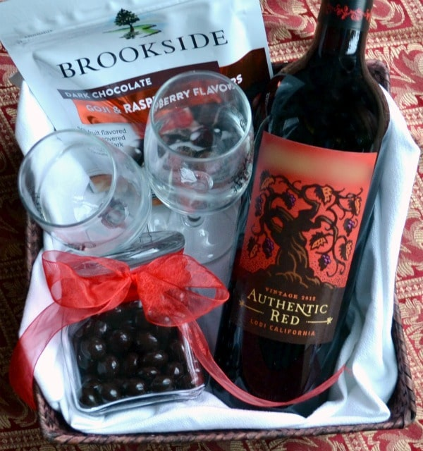 a gift basket with a bag of Brookside chocolate, two wine glasses, a bottle of red wine and a tin of chocolates wrapped with a red ribbon