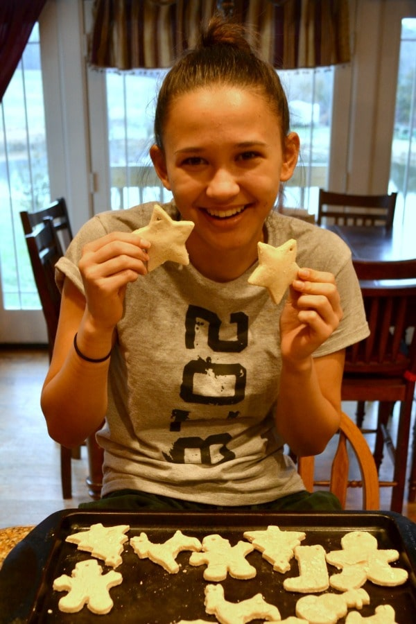 a teen girl holding two salt dough ornaments with more ornaments on a baking pan on the table in front of her with a dining room in the background