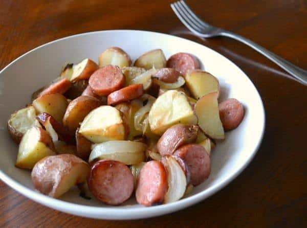 sausage, potatoes and onions in a white bowl next to a fork on a brown table