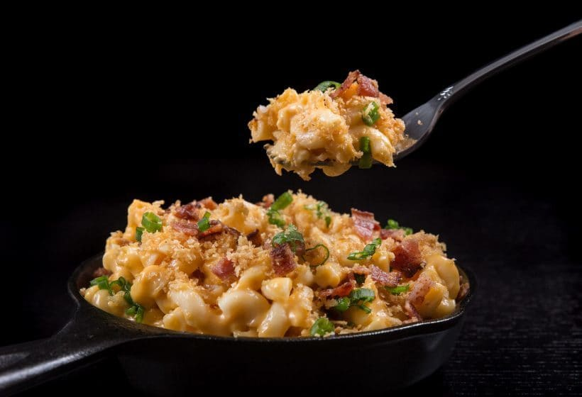 loaded instant pot mac and cheese in a skillet with a fork full of food above it on a black background