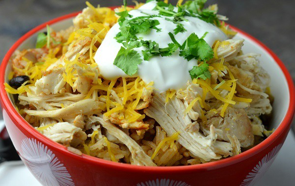chicken taco bowl topped with sour cream in a red bowl