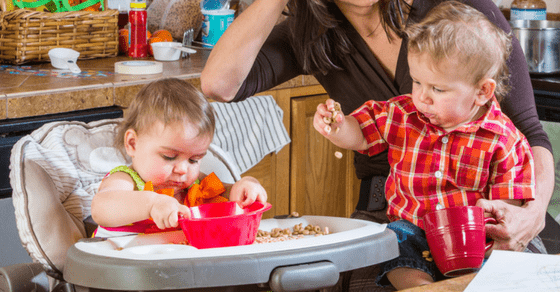a mom in a kitchen holding a boy on her lap next to a girl in a highchair